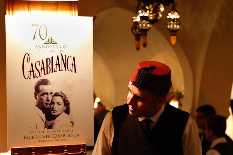 "A Rick's Cafe's server looks at the poster announcing the 70th anniversary tribute to the 1942 movie ""Casablanca"" , in Casablanca, Morocco, Saturday, Nov. 24, 2012.  A former U.S. diplomat spent two years of work and a million dollars in investments to bring Rick's Cafe to Morocco's largest city. The elegant nightclub where Humphrey Bogart pined for Ingrid Bergman was just a set on a Warner Bros. sound stage in California, the film crew never got anywhere near North Africa. (AP Photo/Abdejalil Bounhar)"