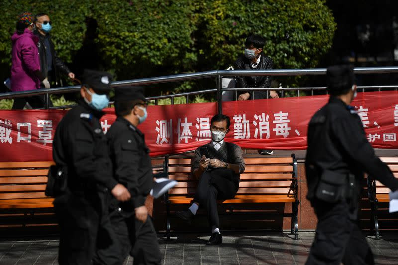 Police officers walk past a man holding his mobile phone while wearing face mask and plastic gloves, on a street in Kunming