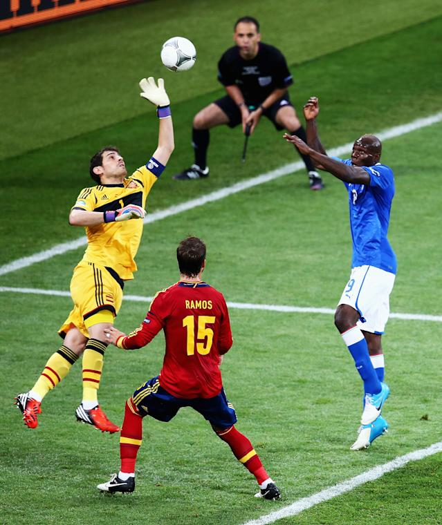 KIEV, UKRAINE - JULY 01: Iker Casillas (L) of Spain stretches for the ball in front of team-mate Sergio Ramos (C) as Mario Balotelli of Italy jumps to head at goal during the UEFA EURO 2012 final match between Spain and Italy at the Olympic Stadium on July 1, 2012 in Kiev, Ukraine. (Photo by Martin Rose/Getty Images)
