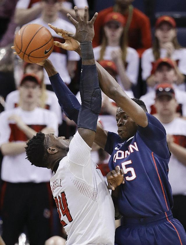 Connecticut center Amida Brimah (35) passes through the reach of Louisville forward Montrezl Harrell (24) during the first half of an NCAA college basketball game in the finals of the American Athletic Conference men's tournament Saturday, March 15, 2014, in Memphis, Tenn. (AP Photo/Mark Humphrey)