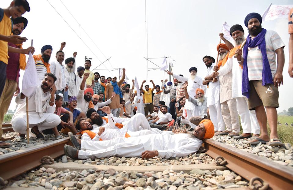 Farmers raise slogans while occupying a railway track during 'rail roko' protest against the passing of agriculture reform bills in the Parliament, at Devi Dasspura village, on September 25, 2020 in Amritsar, India. The two bills - the Farmers (Empowerment and Protection) Agreement on Price Assurance and Farm Services Bill, 2020 and the Farming Produce Trade and Commerce (Promotion and Facilitation) Bill, 2020 - were passed by the Rajya Sabha despite uproar and strong protest by the Opposition parties in the house. (Photo by Sameer Sehgal/Hindustan Times via Getty Images)