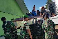Indonesian soldiers prepare coffins for construction workers believed to have been shot dead (AFP Photo/STAF STEEL)