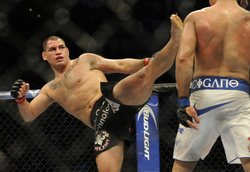 UFC heavyweight champion Cain Velasquez, left, delivers a kick to Junior Dos Santos in a fight for the UFC World Heavyweight title in Houston, Saturday, Oct. 19, 2013. (AP Photo/Pat Sullivan)