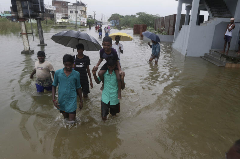 Boys wade through a flooded street on the outskirts of Chennai, Tamil Nadu state, India, Monday, Dec. 2, 2019. The government of the southern Indian state of Tamil Nadu says at least 25 people have died in recent floods that inundated low-lying areas and hundreds more have been evacuated to relief camps. (AP Photo/R. Parthibhan)