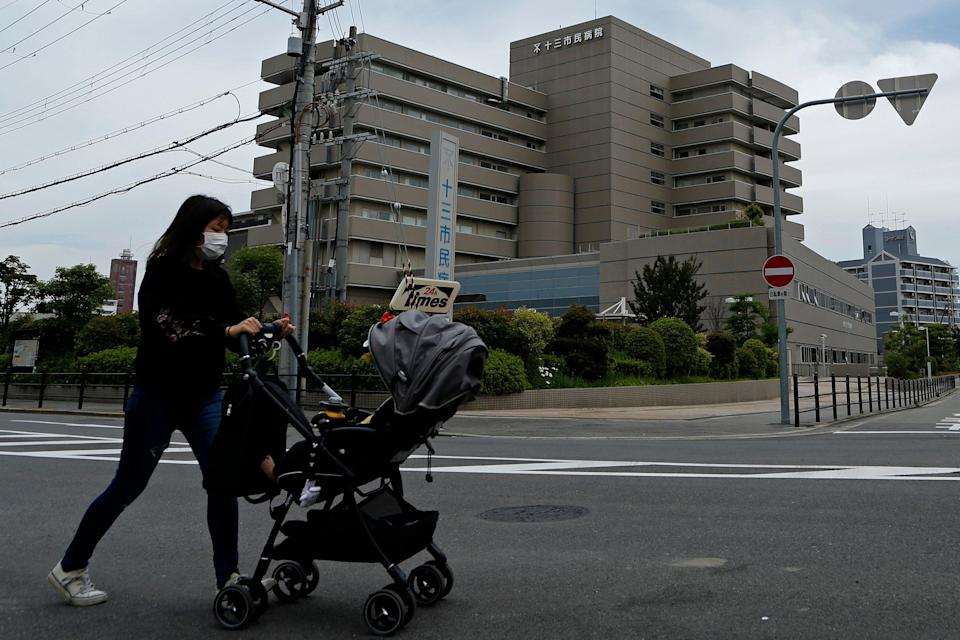 <p>A woman wearing a protective face mask pushes a baby stroller outside the Osaka City Juso Hospital  </p> (Photo by Buddhika Weerasinghe/Getty Images)