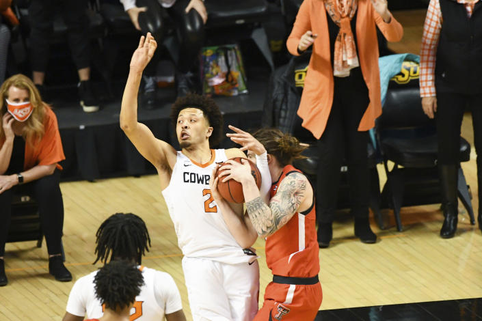 Oklahoma State guard Cade Cunningham (2) attempts to shoot in the final seconds of regulation play while being tied up by Texas Tech guard Avery Benson (21) during an NCAA college basketball game Monday, Feb. 22, 2021, in Stillwater, Okla. (AP Photo/Brody Schmidt)