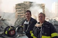 Two fire marshals from the New York Fire Department stand among the rubble. (Caters)