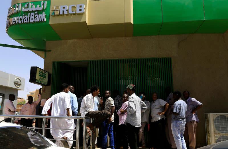 FILE PHOTO: People queue to withdraw money from an ATM in Khartoum