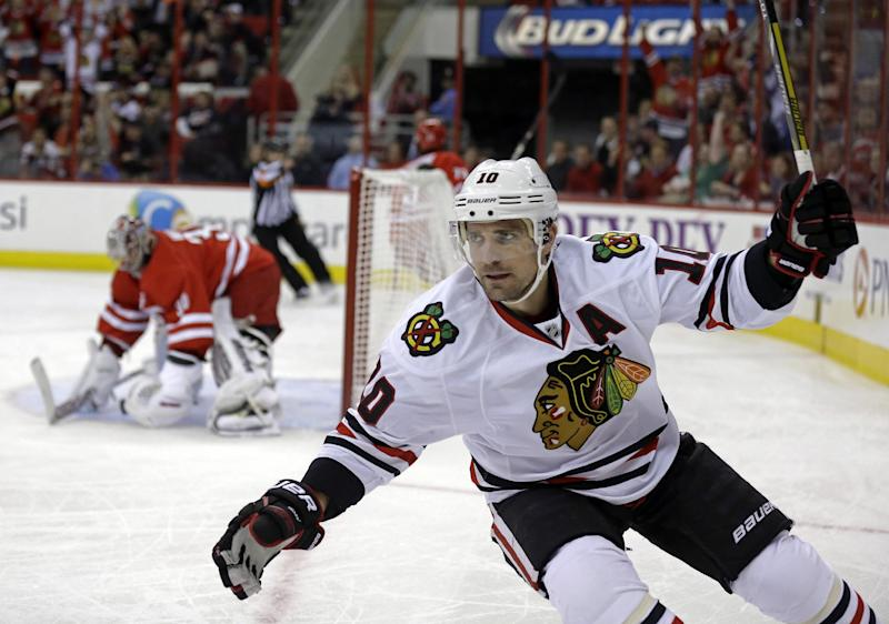 Chicago Blackhawks' Patrick Sharp (10) celebrates his goal against Carolina Hurricanes goalie Cam Ward, rear, during the first period of an NHL hockey game in Raleigh, N.C., Tuesday, Oct. 15, 2013. (AP Photo/Gerry Broome)