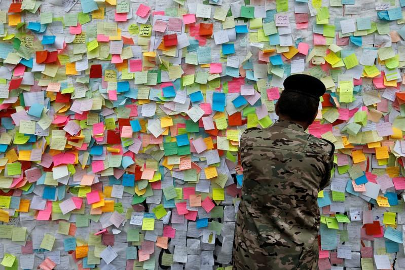 A member of Iraqi security forces pastes a note with his wish at a wall of wishes, during ongoing anti-government protests, at the building called 'the Turkish Restaurant Building', in Baghdad