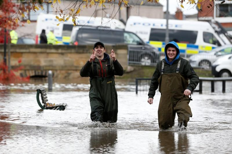 People wade through the floodwater in Bentley, north of Doncaster