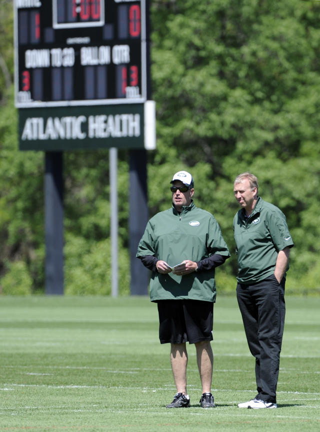 New York Jets coach Rex Ryan, left, and general manager John Idzik look on during NFL football rookie camp Saturday, May 17, 2014, in Florham Park, N.J. (AP Photo/Bill Kostroun)