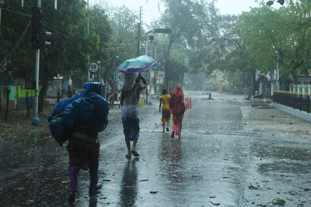 Residents walk along a street to a shelter ahead of the expected landfall of cyclone Amphan in Digha, West Bengal, on May 20, 2020. - India and Bangladesh began evacuating more than two million people on May 18 as a cyclone barrelled towards their coasts, with officials racing to ready extra shelters amid fears of coronavirus contagion in cramped refuges. (Photo by Dibyangshu SARKAR / AFP) (Photo by DIBYANGSHU SARKAR/AFP via Getty Images)
