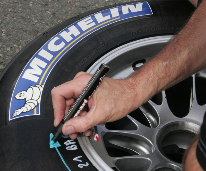 FILE - This June 30, 2005 file photo shows a Michelin team technician writing on a Michelin tire in the paddock at Magny Cours circuit, central France, ahead the French Formula One Grand Prix. Michelin SCA's recent production cuts, made to adjust to sharply falling demand amid the global economic crisis, will cost euro 150 million ($209 million) in the fourth quarter, the French tire maker said Monday Dec.22, 2008. (AP Photo/Michel Spingler)