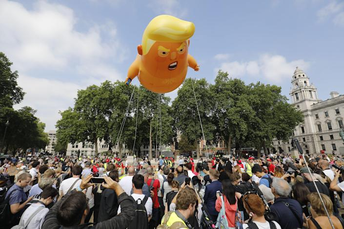 <p>Activists inflate a giant balloon depicting US President Donald Trump as an orange baby during a demonstration against Trump's visit to the UK in Parliament Square in London on July 13, 2018. (Photo: Tolga Akmen/AFP/Getty Images) </p>