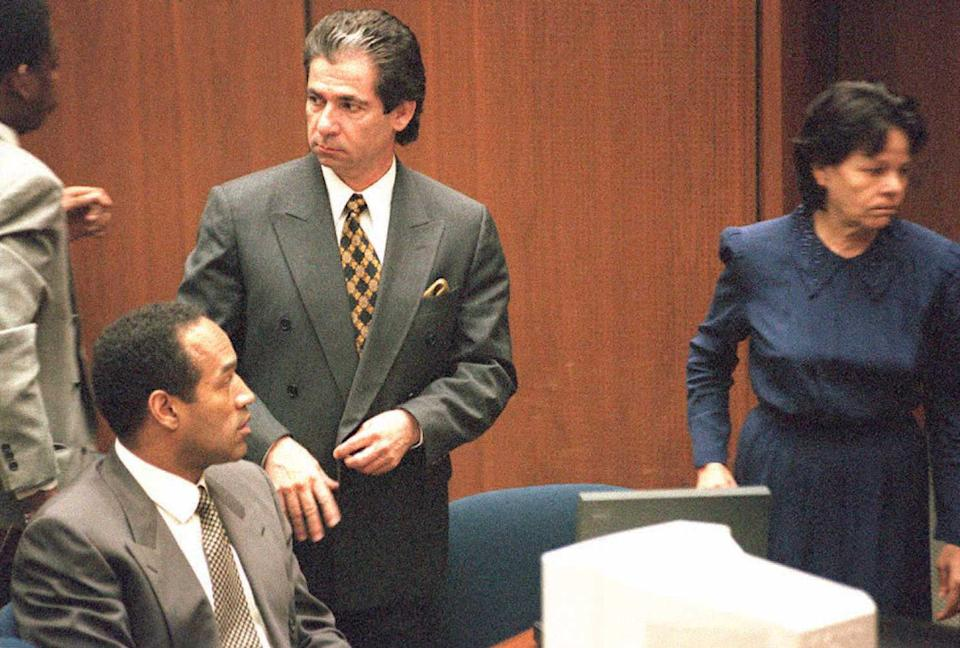 Robert Kardashian stands beside a seated O.J. Simpson in a court room