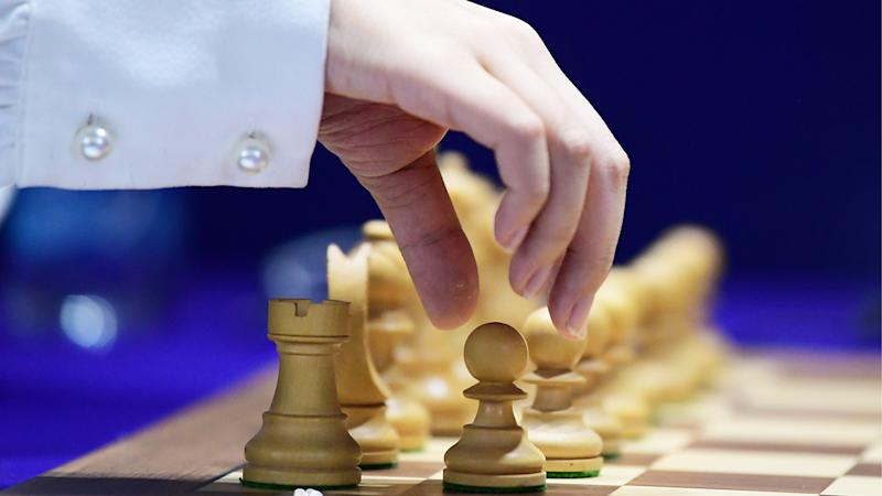 A player is pictured moving a chess piece during the 2020 FIDE Women's World Chess Championship .