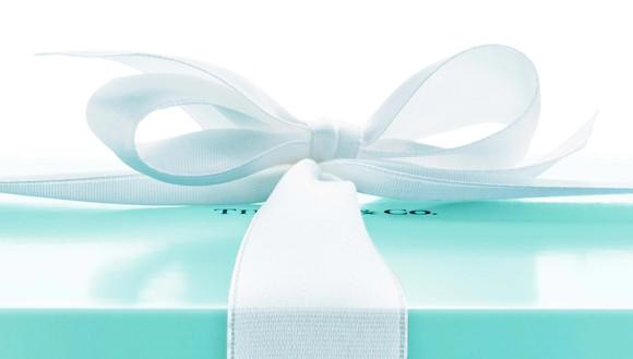 Light blue gift box with white ribbon, with Tiffany & Co. logo partially visible under the bow.
