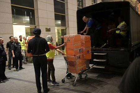A Malaysian police officer pushes a trolley during a raid of three apartments in a condominum owned by former Malaysian prime minister Najib Razak's family, in Kuala Lumpur, May 17, 2018, in this photo taken by The Straits Times. Picture taken May 17, 2018. Ariffin Jamar/The Straits Times via REUTERS