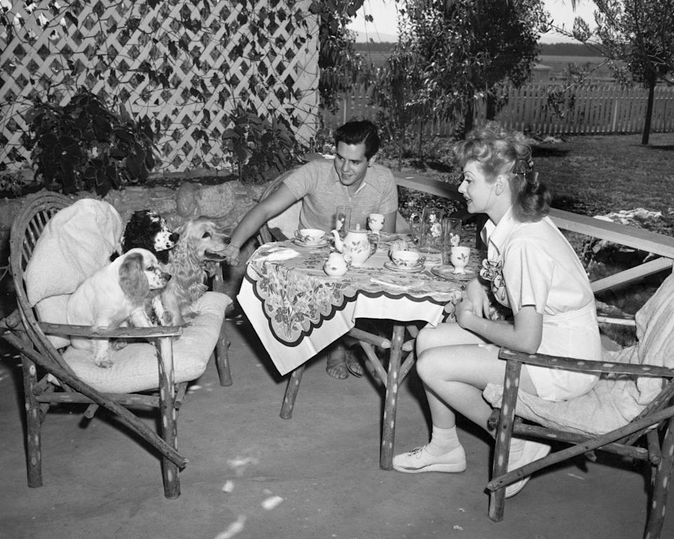 """<p>Newlyweds Lucille Ball and Desi Arnaz are joined by their three Cocker Spaniels as they enjoy breakfast on the outdoor patio of their <a href=""""https://venturablvd.goldenstate.is/lucy-in-the-valley/"""" rel=""""nofollow noopener"""" target=""""_blank"""" data-ylk=""""slk:California farm, Desilu Ranch"""" class=""""link rapid-noclick-resp"""">California farm, Desilu Ranch</a>. In addition to their dogs, the MGM actress's five acre farm included a cow and a flock of chickens. </p>"""