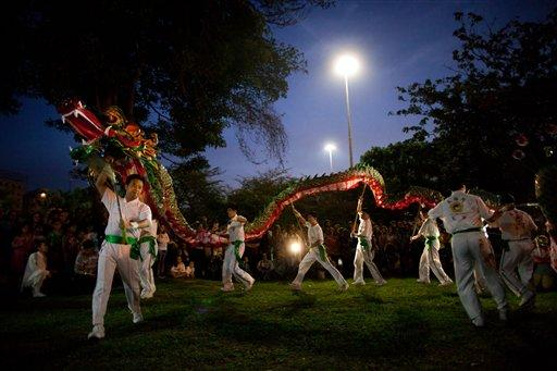 People carry a dragon as they perform the Dragon dance at the People's Summit for Social and Environmental Justice in defense of the commons, a parallel event taking place alongside the United Nations Conference on Sustainable Development, or Rio 20, in Rio de Janeiro, Brazil, Sunday June 17, 2012. (AP Photo/Felipe Dana)
