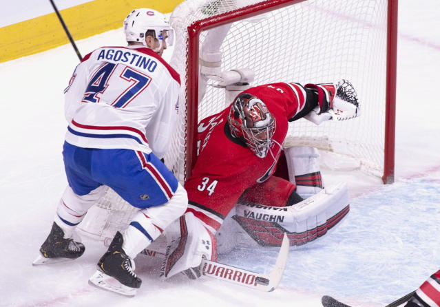 Carolina Hurricanes goaltender Petr Mrazek deflects a shot as Montreal Canadiens' Kenny Agostino looks for a rebound during first period NHL hockey action in Montreal on Thursday, Dec. 13, 2018. (Paul Chiasson/The Canadian Press via AP)