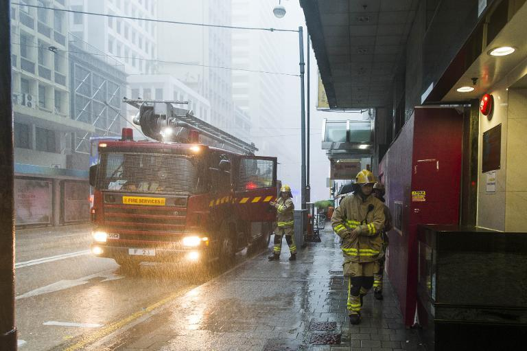 Firemen attend an emergency call in Western District in Hong Kong during a thunderstorm caused by Typhoon Kalmaegi on September 16, 2014