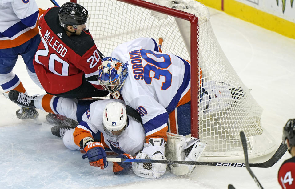 New Jersey Devils center Michael McLeod (20) and New York Islanders center Anders Lee (27) collide with Islanders goaltender Ilya Sorokin (30) in the net during the second period of an NHL hockey game, Sunday, Jan. 24, 2021, in Newark, N.J. (AP Photo/Kathy Willens)