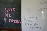 """The Spanish phrase """"Happy Day Teacher,"""" left, hangs next to a white board of words in the Indigenous Quechua language, during language class at a public primary school in Licapa, Peru, Wednesday, Sept. 1, 2021. More than 1.2 million children receive bilingual education in Spanish and Indigenous languages across Peru, a nation of about 32 million people. (AP Photo/Martin Mejia)"""