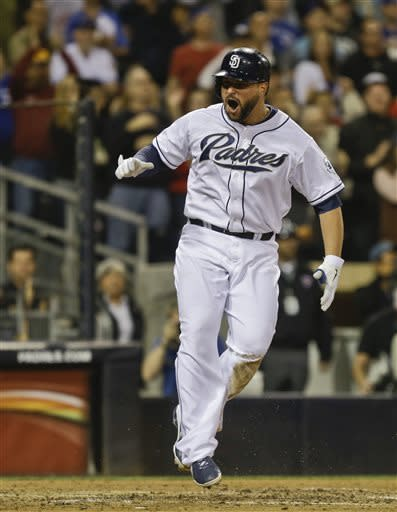San Diego Padres' Yonder Alonso bounces up from his slide after scoring against the Toronto Blue Jays on a double by Jedd Gyorko in the fifth inning of a baseball game in San Diego, Friday, May 31, 2013. (AP Photo/Lenny Ignelzi)