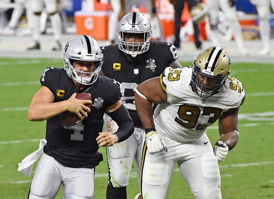 LAS VEGAS, NEVADA - SEPTEMBER 21:  Quarterback Derek Carr #4 of the Las Vegas Raiders rushes under pressure from defensive tackle David Onyemata #93 of the New Orleans Saints ahead of Rodney Hudson #61 of the Raiders during the first half of the NFL game at Allegiant Stadium on September 21, 2020 in Las Vegas, Nevada. The Raiders defeated the Saints 34-24.  (Photo by Ethan Miller/Getty Images)