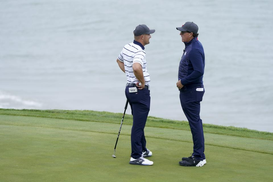 Team USA's Bryson DeChambeau talks to Phil Mickelson on the third hole during a practice day at the Ryder Cup at the Whistling Straits Golf Course Tuesday, Sept. 21, 2021, in Sheboygan, Wis. (AP Photo/Charlie Neibergall)
