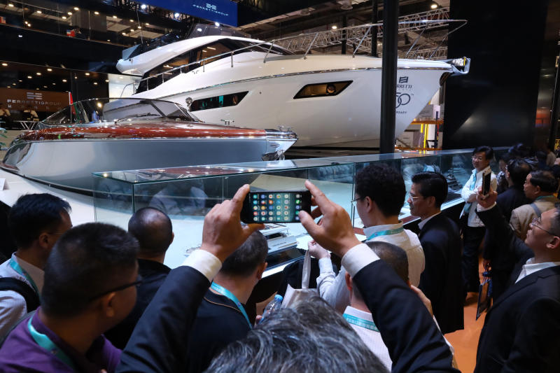 In this Nov. 6, 2018, photo, visitors gather around an Italian Yacht displayed at the China International Import Expo in Shanghai. Visitors to the vast trade fair meant to rebrand China as a welcoming import market could sip Moroccan wine, ogle Italian yachts and watch a Japanese industrial robot play ping-pong. (AP Photo/Ng Han Guan)