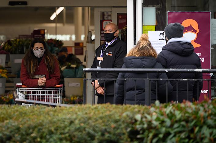LONDON, UNITED KINGDOM - JANUARY 12: A security guard (C) stands at the entrance to a branch of the Sainsbury's supermarket chain following the company's decision to enforce the mandatory wearing of face masks in their stores, on January 12, 2021 in London, United Kingdom. In response to government ministers voicing concerns about the public's behaviour in supermarkets, Sainsbury's and Morrisons have both announced they will be enforcing rules on mask-wearing in their stores. The daily admissions to hospitals of coronavirus cases  has topped 4000 and the current number of patients in hospital with the virus is 32,294. (Photo by Leon Neal/Getty Images)