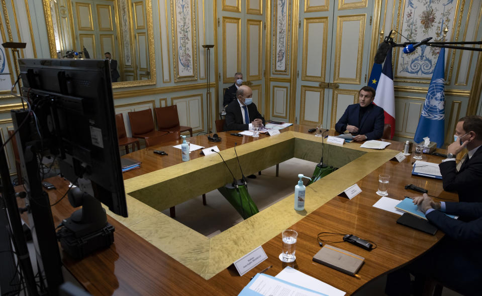French President Emmanuel Macron, right, makes introductory remarks during a visio-conference meeting about support and aid for Lebanon, at the Elysee Palace in Paris, France, Wednesday, Dec. 2, 2020. France is hosting an international video conference on humanitarian aid for Lebanon amid political deadlock in Beirut that has blocked billions of dollars in assistance for the cash-strapped country. (Ian Langsdon, Pool via AP)
