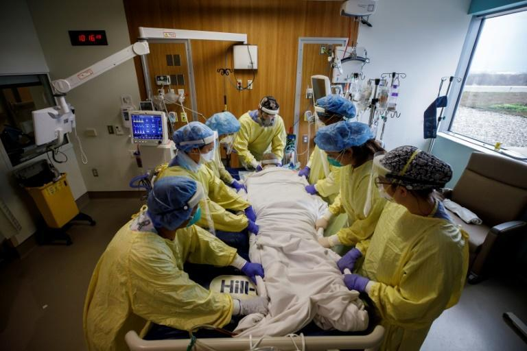 Anesthesiologist, Dr. Jason Cyr (C), adjusts ventilator tubes as health care workers turn a patient suffering from Covid-19 out of prone position at Humber River Hospital's Intensive Care Unit in Toronto, Canada