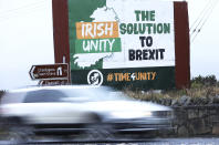 A motorist passes an anti Brexit poster on the Irish border between Republic of Ireland and Northern Ireland, close to the village of Jonnesborough Thursday, Dec. 31, 2020. (AP Photo/Peter Morrison)