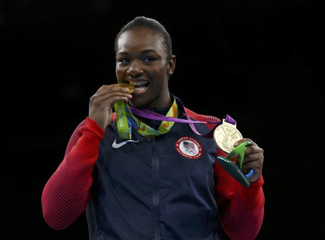 2016 Rio Olympics - Boxing - Victory Ceremony - Women's Middle (75kg) Victory Ceremony - Riocentro - Pavilion 6 - Rio de Janeiro, Brazil - 21/08/2016. Gold medallist Claressa Shields (USA) of USA bites her medal from Rio 2016 while posing with her other medal from London 2012. REUTERS/Peter Cziborra FOR EDITORIAL USE ONLY. NOT FOR SALE FOR MARKETING OR ADVERTISING CAMPAIGNS.