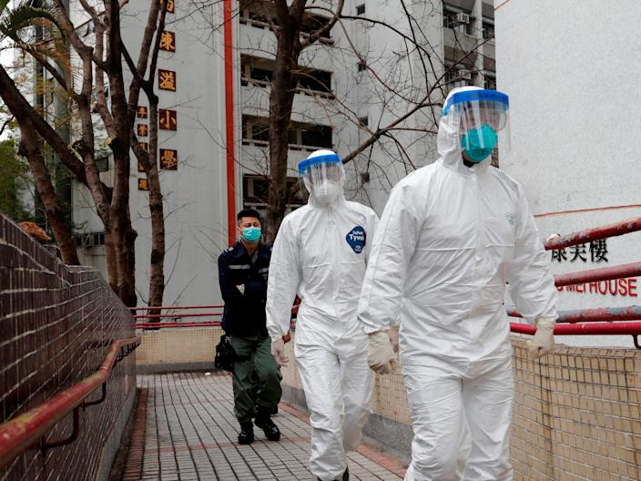 Health workers in protective gears walk as they evacuate residents from a public housing building outside Hong Mei House, at Cheung Hong Estate in Hong Kong