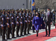 Kosovo newly elected president Vjosa Osmani-Sadriu, center, flanked by speaker of parliament Glauk Konjufca, inspect the Guard of Honour during a presidential hand over ceremony in capital Pristina, Kosovo, on Tuesday, April 6, 2021. Osmani took over the presidency after being elected to the post during a two-day extraordinary session of parliament. (AP Photo/ Visar Kryeziu)