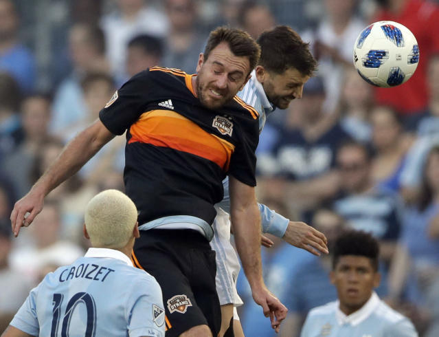Houston Dynamo midfielder Eric Alexander, top left, heads the ball against Sporting Kansas City midfielder Ilie Sanchez, top right, during the first half of an MLS soccer match in Kansas City, Kan., Saturday, June 23, 2018. (AP Photo/Orlin Wagner)