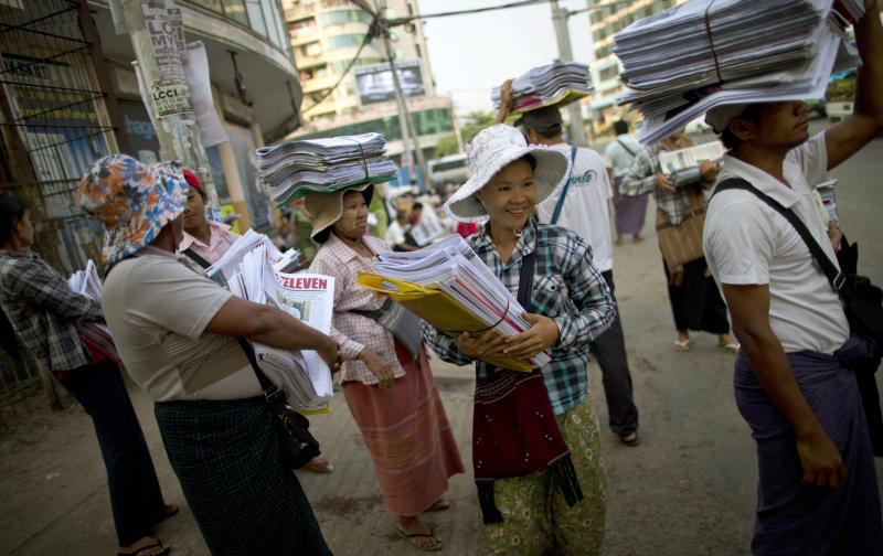 Newspaper sellers wait for a bus after receiving newspapers from a wholesale dispatcher in Yangon, Myanmar, Monday, April 1, 2013. For most people in Myanmar, it will be a novelty when privately run daily newspapers hit the streets on Monday. Many weren't even born when the late dictator Ne Win imposed a state monopoly on the daily press in the 1960s.(AP Photo/Gemunu Amarasinghe)