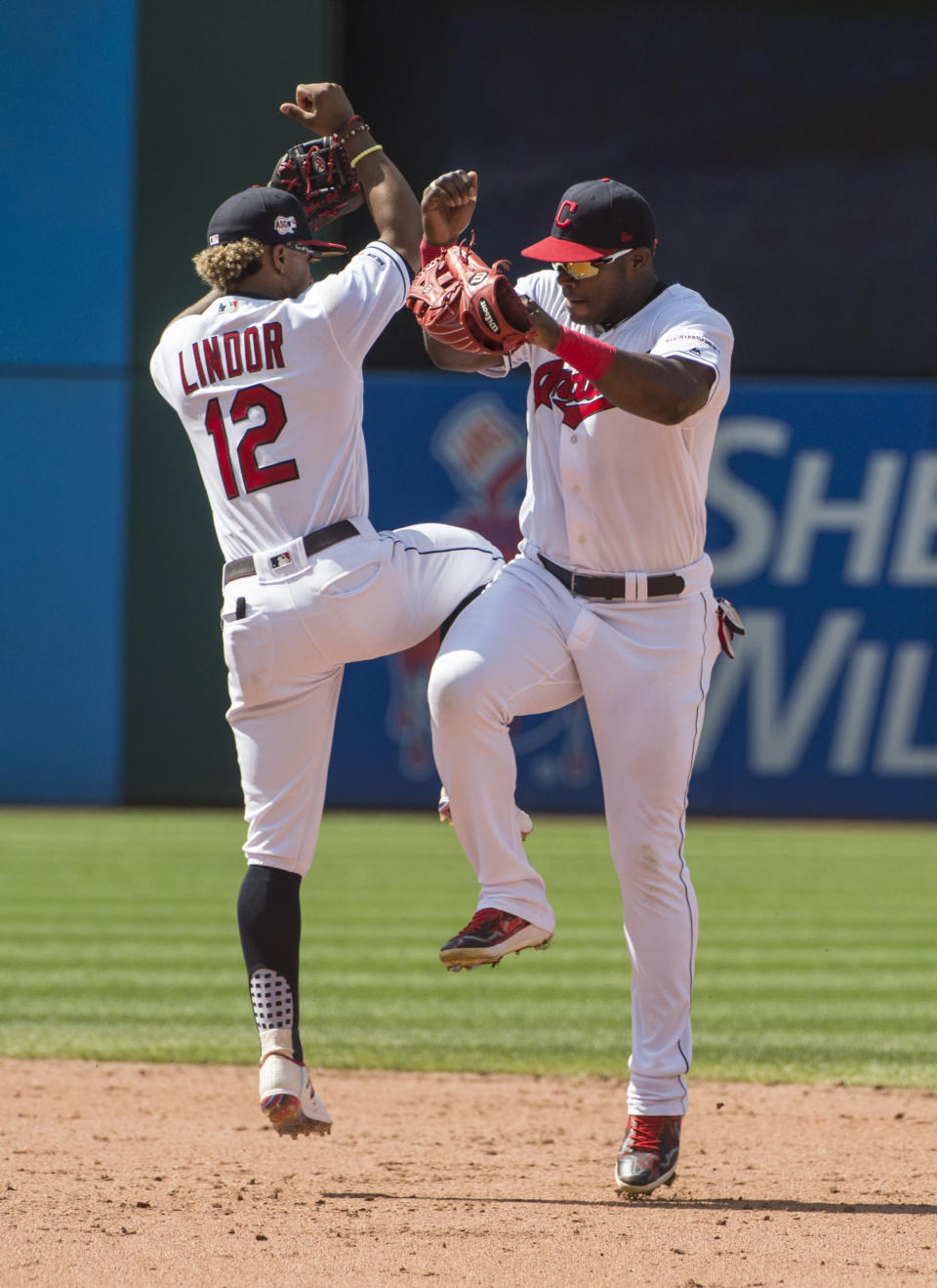 Cleveland Indians' Francisco Lindor and Yasiel Puig celebrate the Indians 2-0 win over the Texas Rangers at the end of the first game of a baseball doubleheader in Cleveland, Wednesday, Aug. 7, 2019. (AP Photo/Phil Long)