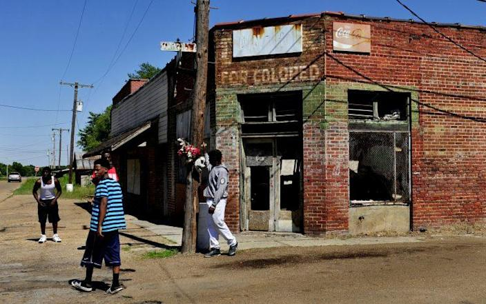 """Young men in Drew, Miss., hang out on the street near a burned-out store painted with the designation """"For Colored,"""" which dates to the era of segregation. (Photo: Michael S. Williamson/The Washington Post via Getty Images)"""