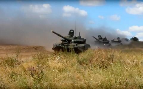Tanks roll during the military exercises in the Chita region, Eastern Siberia, on Tuesday - Credit: AP/Russia War Games