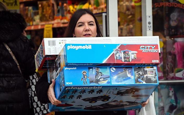 Shoppers leave a Smyths Toys shop with their purchases as many fear the restrictions won't end in time for Christmas shopping - AFP