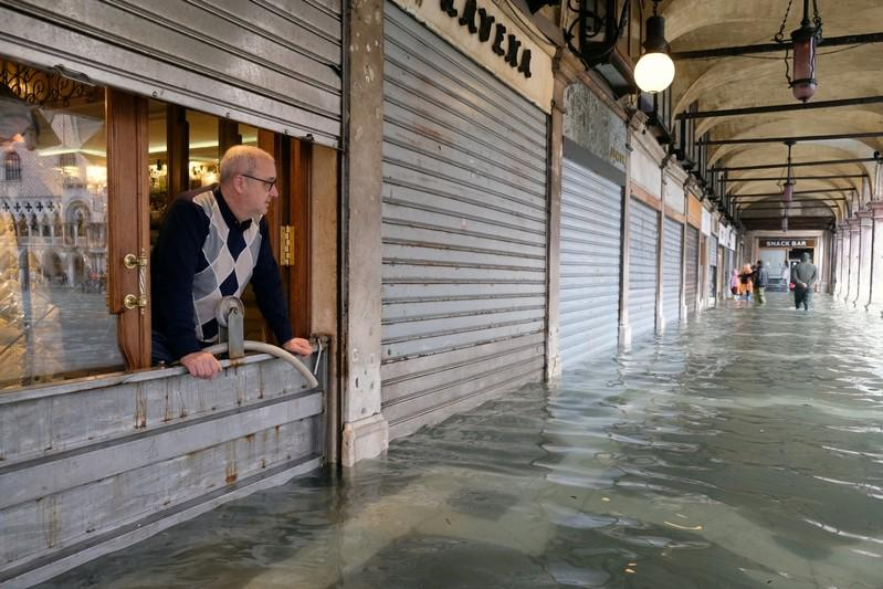 A man stands inside is store in St. Mark's Square after days of severe flooding in Venice