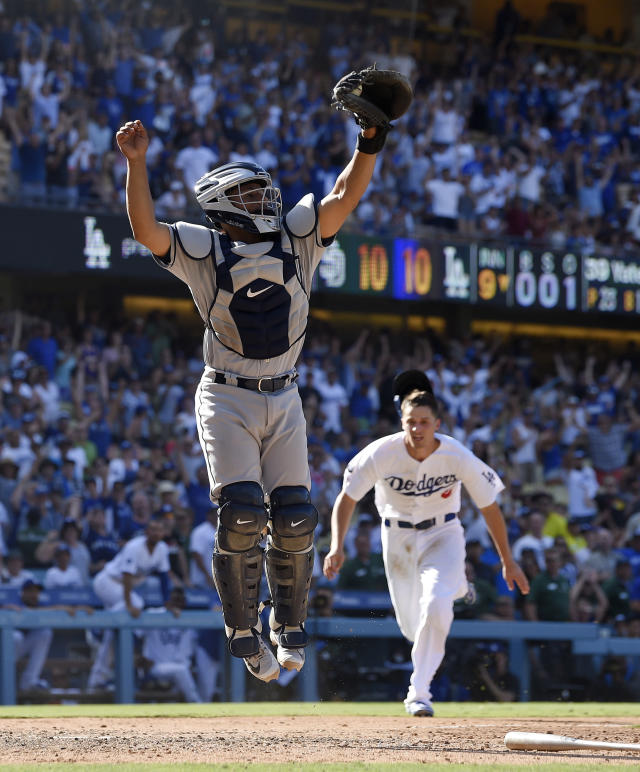 Los Angeles Dodgers' Corey Seager, right, gets set to score the winning run on a walkoff double by Max Muncy as San Diego Padres catcher Francisco Mejia takes a high throw during the ninth inning of a baseball game Sunday, Aug. 4, 2019, in Los Angeles. (AP Photo/Mark J. Terrill)