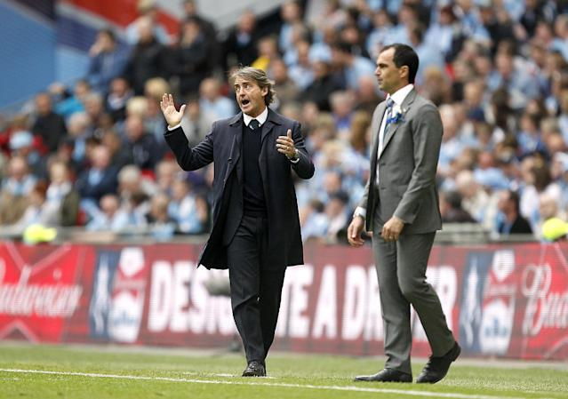 Wigan Athletic manager Roberto Martinez (right) and Manchester City manager Roberto Mancini on the touchline