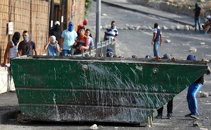 Palestinian youths take shelter behind a garbage container during clashes with Israeli police in the east Jerusalem Arab neighbourhood of Issawiya following unrest at the Al-aqsa mosque compounds on September 13, 2015 (AFP Photo/Ahmad Gharabli)